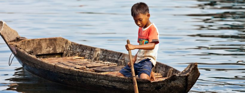 Boy paddling on Tonle Sap Lake